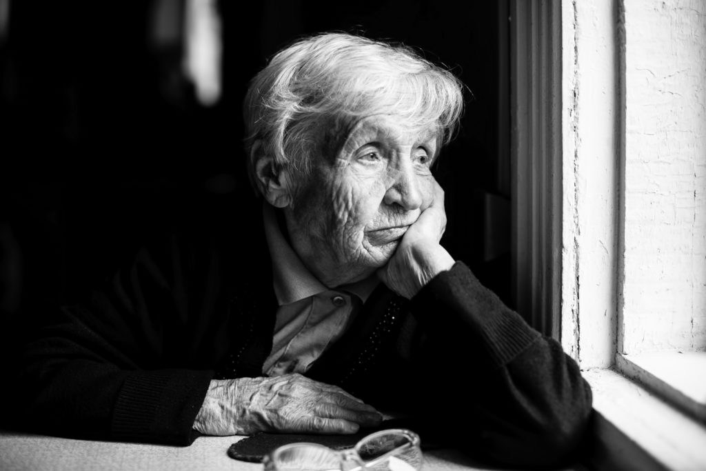 Elderly woman sadly looking out the window, a black-and-white ph