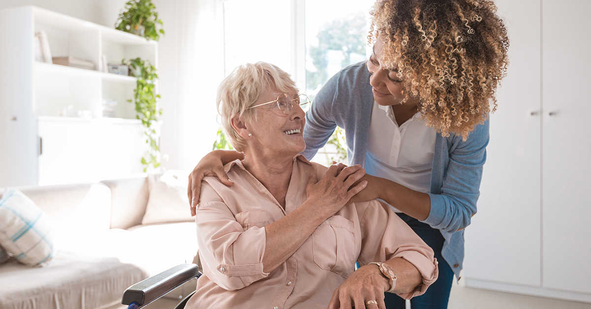 Woman being embraced by another woman in an assisted living environment